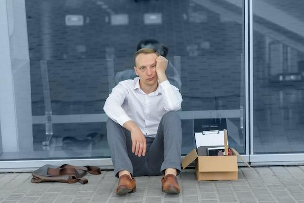 Un giovane impiegato licenziato è seduto sotto il suo ufficio. accanto a lui c'è la sua cartoleria. l'uomo è stressato.