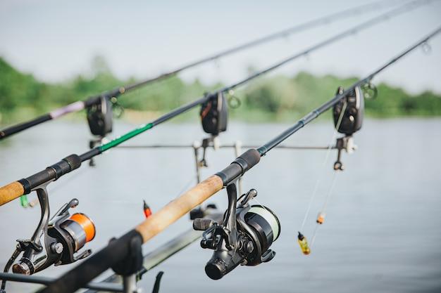 Giovane pescatore che pesca sul lago o sul fiume. immagine di tre canne con attrezzatura completa durante il tempo di pesca. nessuna persona accanto. bobina e richiamo. bella giornata di sole.