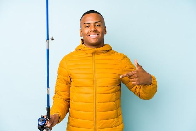 Uomo giovane pescatore isolato su una persona di sfondo blu che punta a mano uno spazio di copia della camicia, orgoglioso e fiducioso