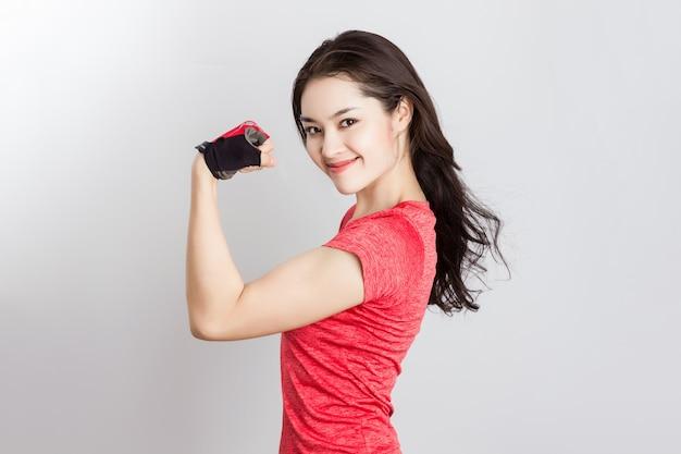 La giovane donna asiatica adatta che indossa i guanti mostra il braccio del bicipite