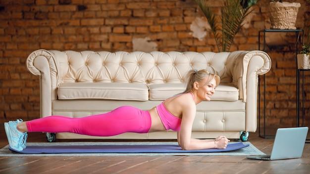 Ragazza giovane blogger in forma che fa la stuoia della plancia in abbigliamento sportivo con la parte superiore del laptop che fa allenamento online a casa, registra tutorial di aerobica online da casa, esercizio sulla fotocamera