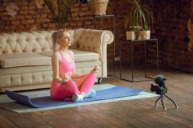 Ragazza giovane blogger in forma seduta sul materassino yoga in tenuta sportiva con fotocamera che fa allenamento online a casa, registra tutorial di aerobica online da casa, esercizio sulla fotocamera