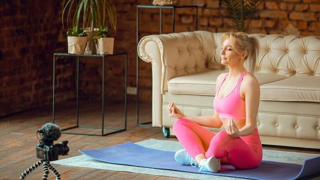 Ragazza giovane blogger in forma seduta sul materassino yoga in tenuta sportiva con fotocamera che fa allenamento online a casa, registra tutorial di aerobica online da casa