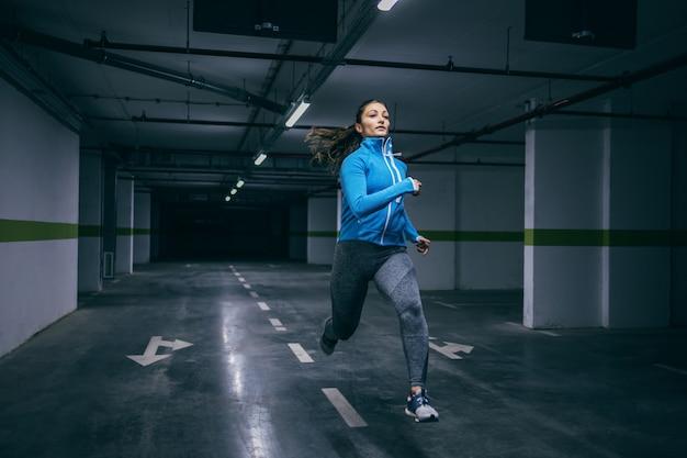 Young fit indoeuropea sportiva in tuta che corre veloce in garage.
