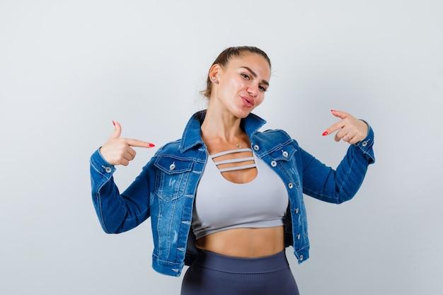 Giovane femmina in forma che indica se stessa in cima, giacca di jeans e sembra allegra. vista frontale.
