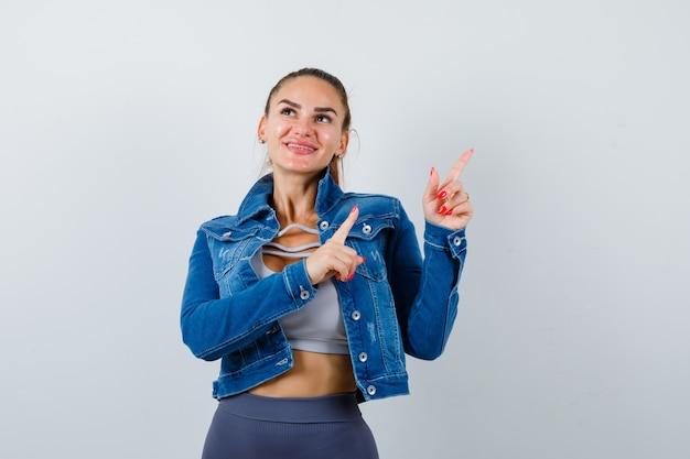 Giovane donna in forma che punta all'angolo in alto a destra mentre distoglie lo sguardo in alto, giacca di jeans e sembra gioiosa, vista frontale.