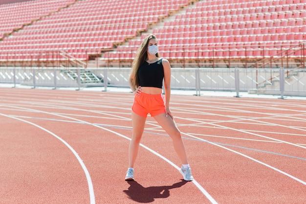 Giovane donna in forma in abbigliamento sportivo e maschera protettiva per il coronavirus su pista rossa e campo da pallavolo durante l'allenamento all'aperto allo stadio
