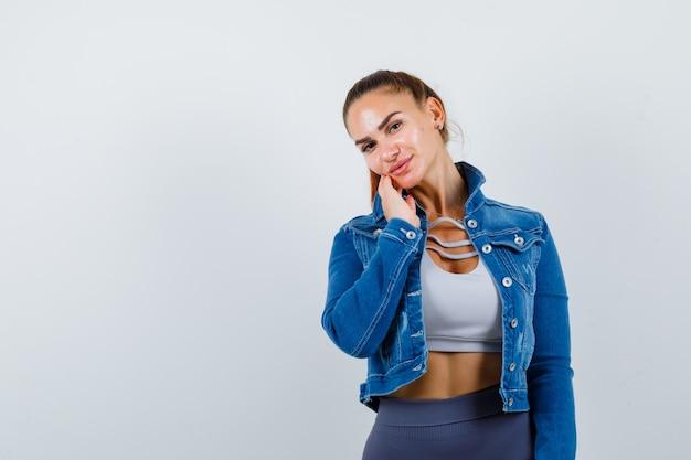 Giovane donna in forma che tocca la guancia con le dita nella parte superiore, giacca di jeans e sembra sicura. vista frontale.
