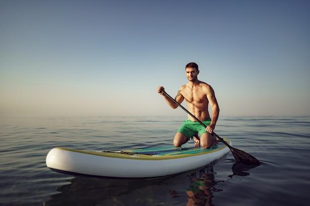 Giovane uomo in forma sulla tavola da paddle che galleggia sul lago