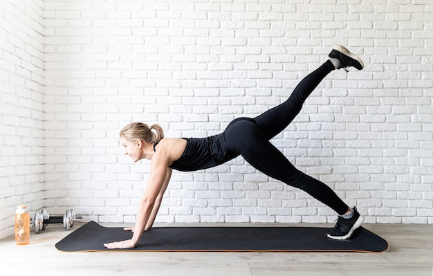 Giovane donna adatta in abiti sportivi neri facendo push up a casa