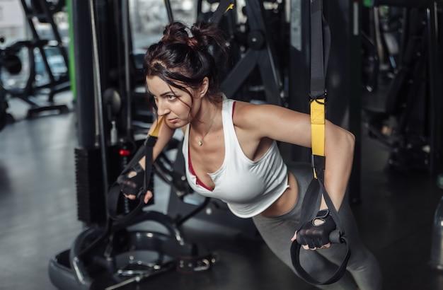 Giovane donna adatta praticando push up con corde fitness in palestra