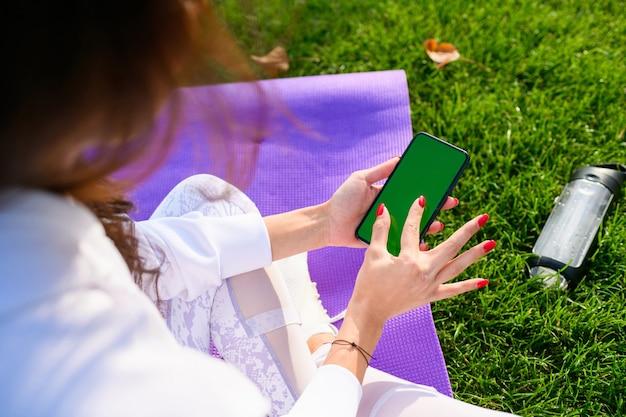 La giovane donna in forma si siede al tappetino sportivo viola nel parco, tiene in mano lo smartphone e ingrandisce lo schermo durante l'allenamento, il fitness all'aperto. smartphone mobile con schermo verde.