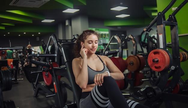 Giovane donna adatta che si siede su una panchina in palestra. guarda l'orologio e tocca gli auricolari. gadget moderni. riposa tra gli esercizi.