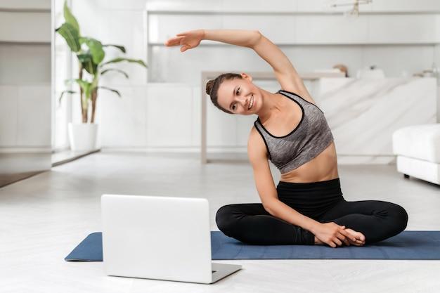 Giovane donna adatta in abiti sportivi che praticano yoga a casa con formazione online su laptop, guardando lezioni virtuali ed esercitazioni