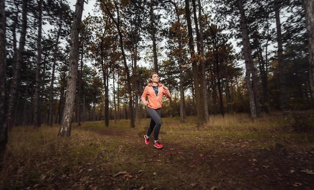 La giovane donna adatta in abbigliamento sportivo corre lungo il sentiero nel bosco