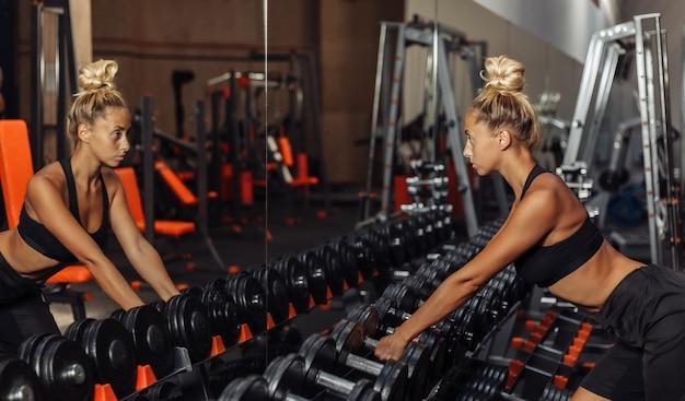 La donna adatta dei giovani in abiti sportivi prende le teste di legno da uno scaffale nella palestra. concetto di stile di vita sano. allenamento del corpo con pesi liberi