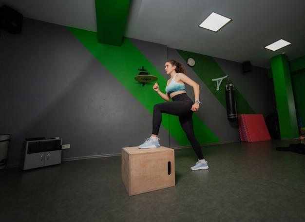 Giovane donna in forma passi su una scatola di legno in una lezione di sport. allenamento funzionale, allenamento.