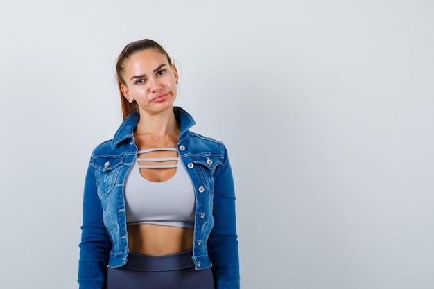 Giovane donna in forma in cima, giacca di jeans e sembra sconvolta. vista frontale.