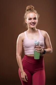 Giovane donna in forma in tuta che tiene in mano una bottiglia con un drink mentre fa una breve pausa dopo l'allenamento sportivo su marrone in isolamento