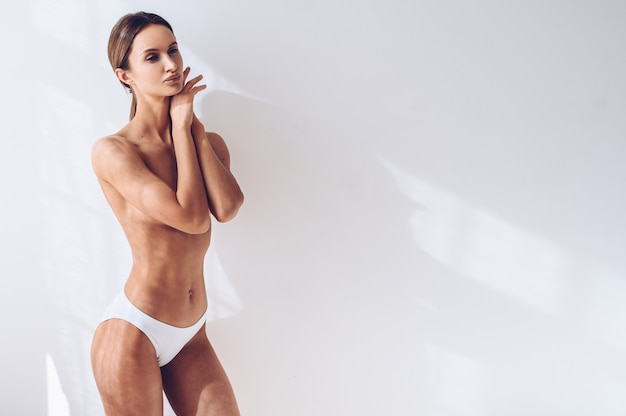 Donna adatta dei giovani in biancheria bianca sulla parete bianca isolata. femmina attraente muscolare esile con la pancia piatta. copia spazio per il testo. cura del corpo, vita sana e sportiva, depilazione, concetto di yoga