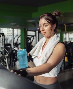 Giovane donna adatta con un asciugamano sulle spalle tenendo la bottiglia d'acqua su un tapis roulant. concetto di perdita di peso, allenamento aerobico
