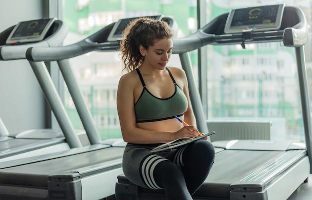Una giovane donna in forma scrive informazioni in un libro di formazione per ulteriori progressi nell'allenamento in palestra. concetto di stile di vita sano. il tuo piano di allenamento