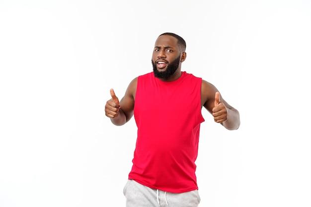 Giovane uomo di colore africano fitness in abbigliamento sportivo tifo spensierato ed eccitato. concetto di vittoria.