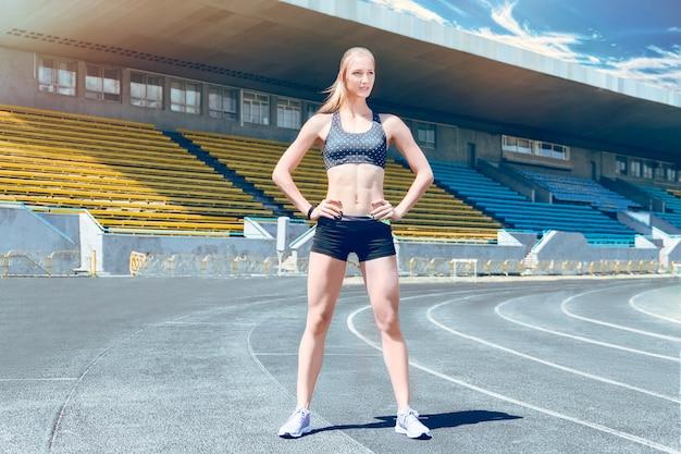 Giovane donna del corridore del muscolo dell'atleta di forma fisica che fa gli exersices sullo stadio.