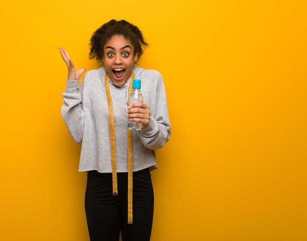 Giovane donna nera di forma fisica che celebra una vittoria o un successo. che tiene una bottiglia di acqua.