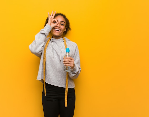 Giovane donna di colore di forma fisica fiducioso che fa gesto giusto sull'occhio. holding una bottiglia di acqua.