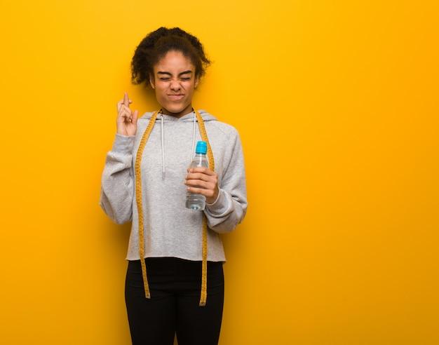 Dita dell'incrocio della giovane donna di colore di forma fisica per avere fortuna. tenere una bottiglia di acqua.