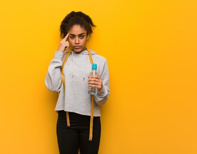 Donna di colore giovane fitness facendo un gesto di concentrazione. tenere una bottiglia d'acqua.