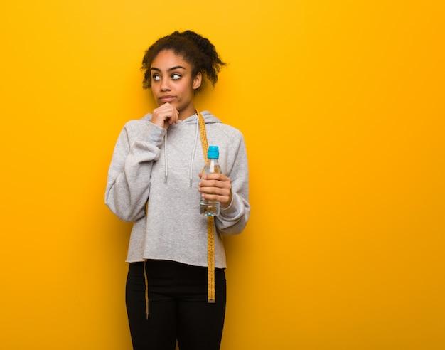 Giovane donna di colore di forma fisica che dubita e confusa. possedendo una bottiglia di acqua.