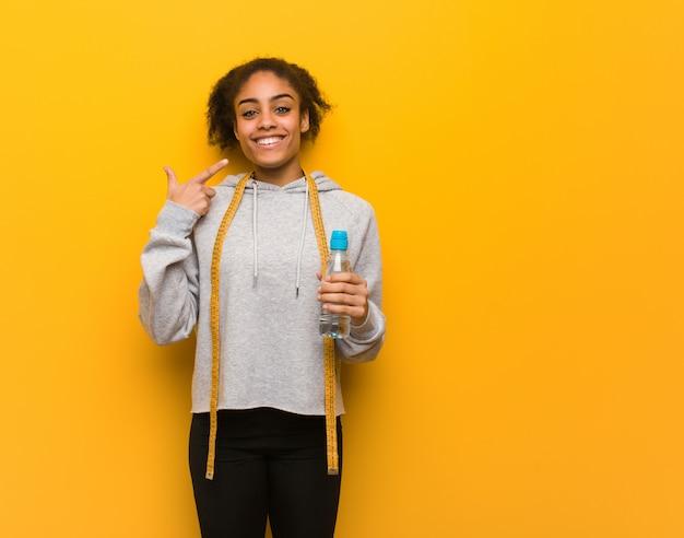Sorrisi di giovane donna di colore fitness, indicando la bocca. tenere una bottiglia d'acqua.