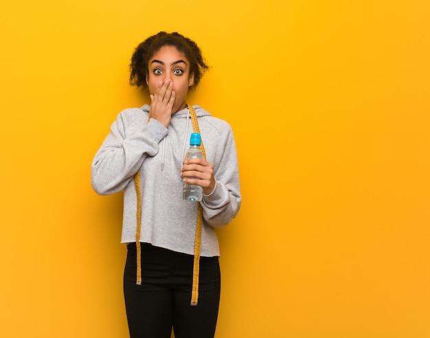 Giovane donna di colore fitness molto spaventata e paura nascosta. tenendo una bottiglia d'acqua.