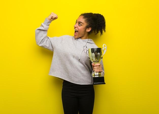 Giovane donna di colore fitness che non si arrende. tenendo un trofeo.