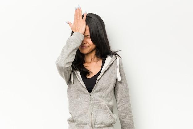 Giovane donna cinese di forma fisica che dimentica qualcosa, schiaffeggiando la fronte con il palmo e chiudendo gli occhi.