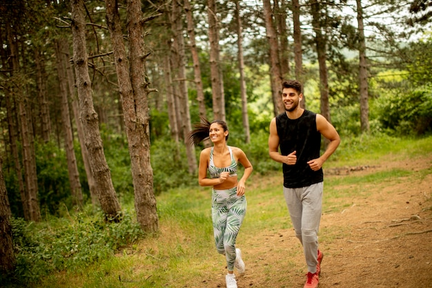 Coppia giovane fitness in esecuzione presso il sentiero nel bosco in una giornata estiva