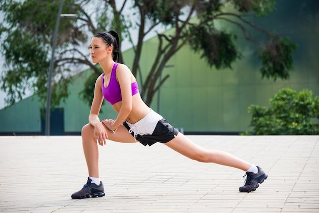 Giovane ragazza fitness facendo esercizi di stretching all'aperto