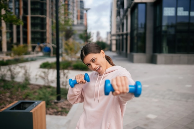 Giovane ragazza fitness che fa esercizi con manubri nel parco cittadino