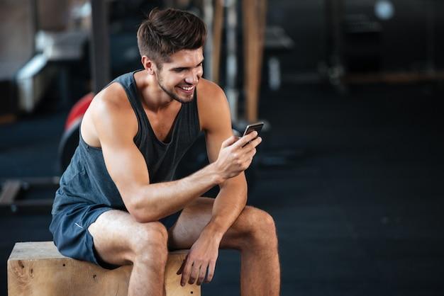 Il giovane uomo di forma fisica si siede sulla scatola e guarda il telefono