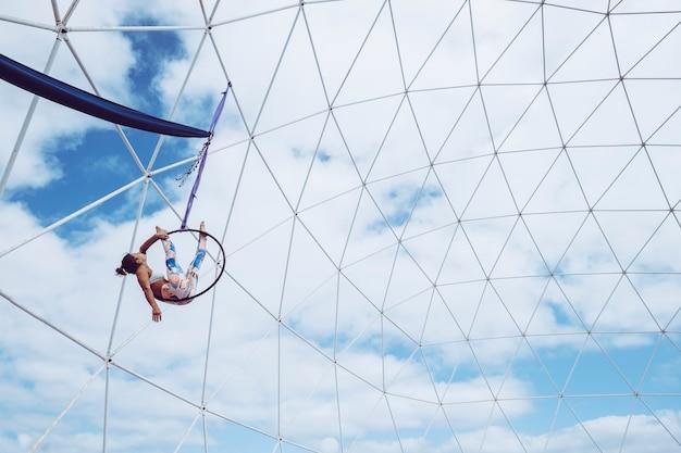 L'atleta della ragazza della gente del corpo perfetto di forma fisica giovane fa gli esercizi aerei con un cerchio