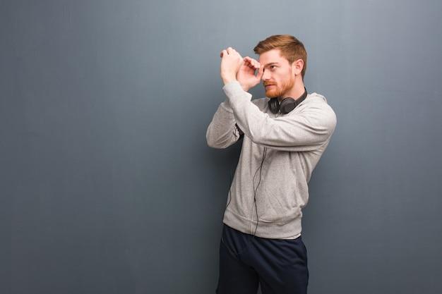 Uomo giovane rossa di forma fisica che fa il gesto di un cannocchiale