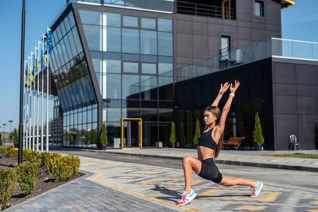 Giovane donna fitness facendo esercizi di yoga di stretching vicino al moderno edificio della città. uno stile di vita sano