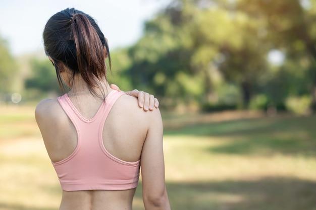 Giovane donna fitness tenendo la sua spalla infortunio sportivo, muscolo doloroso durante l'allenamento. femmina corridore asiatico che ha problemi di corpo dopo l'esercizio fuori in estate