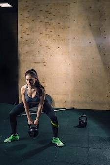 Giovane donna di forma fisica che solleva la campana pesante del bollitore alla palestra