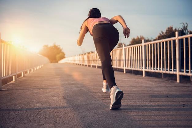 Giovane atleta del corridore della donna di forma fisica che corre sulla strada al tramonto