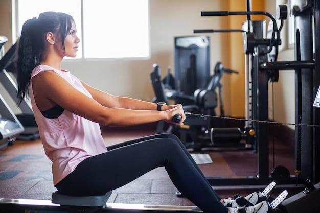 Giovane donna fitness allenandovi in palestra
