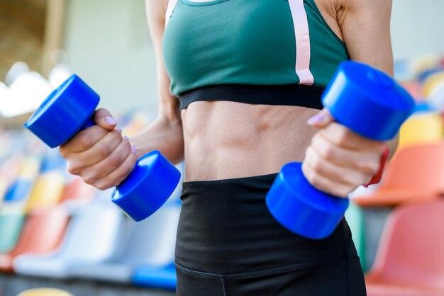 Giovane donna fitness che si allena con i manubri nello stadio della città. concetto di sport
