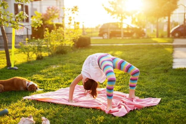 La giovane ragazza flessibile sta eseguendo una posa del ponte di yoga su una coperta sull'erba mentre il suo cane la sta guardando.